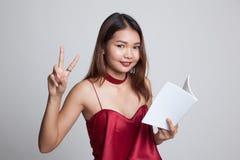 Молодой азиатский знак Виктора выставки женщины с книгой Стоковое фото RF