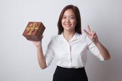 Молодой азиатский знак победы выставки женщины с подарочной коробкой Стоковое Фото