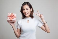 Молодой азиатский знак победы выставки женщины с подарочной коробкой Стоковое фото RF