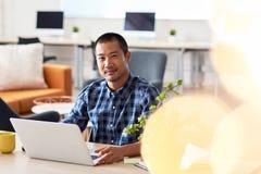 Молодой азиатский дизайнер работая на компьтер-книжке в офисе Стоковая Фотография