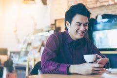 Молодой азиатский красивый бизнесмен усмехаясь пока читающ его умное Стоковое Изображение RF