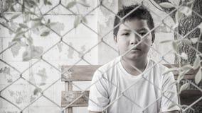 Молодой азиатский мальчик сидя самостоятельно в парке Стоковое Изображение RF