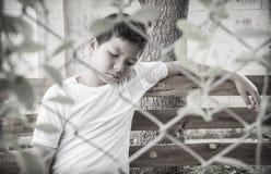 Молодой азиатский мальчик сидя самостоятельно в парке Стоковые Изображения RF