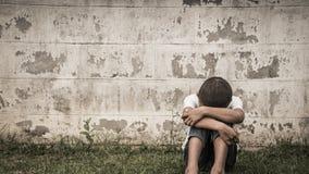 Молодой азиатский мальчик сидя самостоятельно в парке Стоковое Фото
