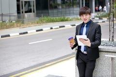 Молодой азиатский мужской руководитель бизнеса используя ПК таблетки стоковая фотография rf