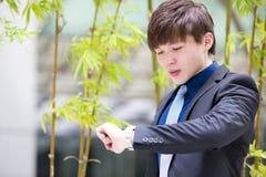 Молодой азиатский мужской руководитель бизнеса смотря время стоковые изображения rf