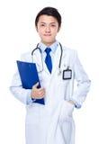 Молодой азиатский доктор с доской сзажимом для бумаги Стоковые Изображения RF