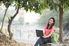 Молодой азиатский сидеть студента внешний, используя компьтер-книжку Стоковое Фото