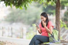 Молодой азиатский сидеть студента внешний, читающ что-то на cellph стоковая фотография