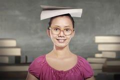 Молодой азиатский студент женщины в стеклах с книгой на ее голове Стоковое фото RF