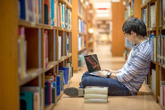 Молодой азиатский студент университета в библиотеке Стоковое Изображение