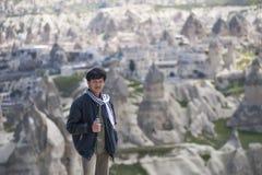 Молодой азиатский турист человека на верхней части горы на Cappadocia стоковые фотографии rf