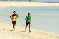Молодой азиатский человек бежать на пляже, концепции спорта стоковые фото
