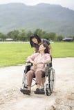 Молодой азиат принимает заботе старшую женщину с кресло-коляской Стоковое Фото