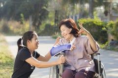 Молодой азиат принимает заботе старшую женщину Стоковые Фотографии RF