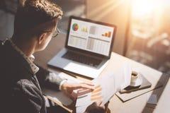 Молодой аналитик финансового рынка в eyeglasses работая на солнечном офисе на компьтер-книжке пока сидящ на деревянном столе Бизн