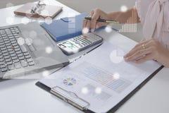 Молодой аналитик финансового рынка работая на офисе на компьтер-книжке пока сидящ на белой таблице Бизнесмен анализирует документ Стоковая Фотография