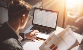 Молодой аналитик финансов банка в eyeglasses работая на солнечном офисе на компьтер-книжке пока сидящ на деревянном столе Бизнесм стоковое изображение