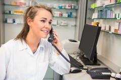 Молодой аптекарь на телефоне стоковые изображения