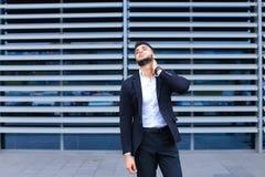Молодой арабский человек показывает утомлянную боль шеи в деловом центре Стоковые Фотографии RF