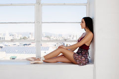 Молодой артист балета сидит на предпосылке окна Стоковое Изображение RF
