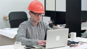 Молодой архитектор работая на компьтер-книжке в офисе сток-видео