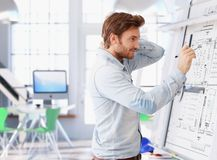 Молодой архитектор работая на чертежной доске Стоковые Изображения RF