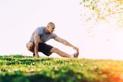 Молодой атлетический бегун делая протягивающ тренировку, подготавливая для разминки в парке Заход солнца Стоковое фото RF