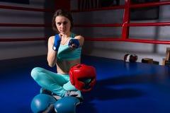 Молодой атлетический женский боксер сидя и обхватывая ее кулаки стоковое фото rf
