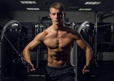 Молодой атлетический человек нагнетая вверх muscles на кроссовере стоковые фото