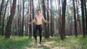 Молодой атлетический человек с чуть-чуть, нагим торсом, скача веревочкой, выполняет тренировки прочности с резиновой веревочкой,  видеоматериал