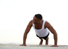 Молодой атлетический человек усмехаясь и делая нажимает поднимает стоковое фото rf