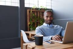 Молодой африканский бизнесмен работая на компьтер-книжке в офисе Стоковые Фото