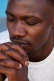Молодой африканский человек моля с руками сжимал и глаза закрыли Стоковая Фотография RF
