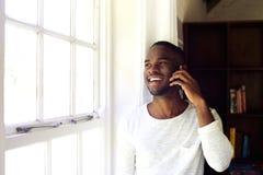 Молодой африканский человек дома звоня телефонный звонок Стоковая Фотография