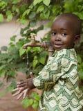 Молодой африканский школьник держа руки под краном Scarci воды стоковое изображение