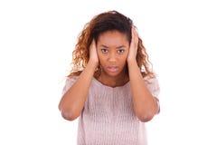 Молодой афроамериканец покрывая ее уши при ее изолированные руки стоковое изображение rf