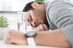 Молодой Афро-американский бизнесмен спать на таблице на современном офисе Стоковые Фотографии RF