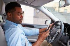Молодой Афро-американский мужской водитель используя телефон, в взгляде автомобиля Стоковые Изображения