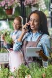 Молодой Афро-американский флорист держа тетрадь и говоря на smartphone пока коллега работая позади в цветочном магазине Стоковая Фотография