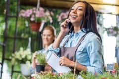Молодой Афро-американский флорист держа тетрадь и говоря на smartphone пока коллега работая позади в цветочном магазине Стоковое Изображение