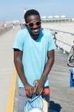 Молодой Афро-американский человек держа скейтборд стоковые изображения