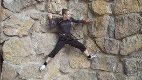 Молодой альпинист утеса в альпинизме тренировки Кавказский человек имеет взбираясь разминку на крытом спортзале утеса альпинисты  сток-видео