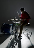 Молодой барабанщик играя в свете contre Стоковая Фотография