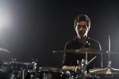 Молодой барабанщик играя набор барабанчика в студии стоковые изображения