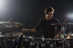 Молодой барабанщик играя набор барабанчика в студии стоковое фото rf