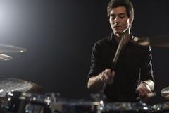 Молодой барабанщик играя набор барабанчика в студии стоковые фото
