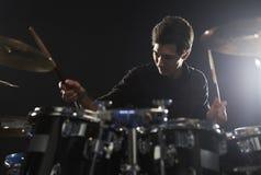 Молодой барабанщик играя набор барабанчика в студии стоковое изображение