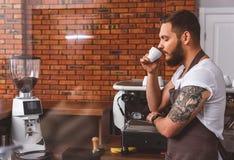 Молодой бармен наслаждаясь ароматностью кофе Стоковое Изображение