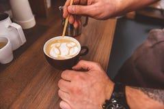 Молодой бармен создавая изображение в чашке latte стоковые изображения